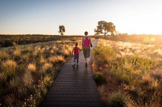 woman and girl wearing pink tank tops walking down paved pathway in large open field at sunset