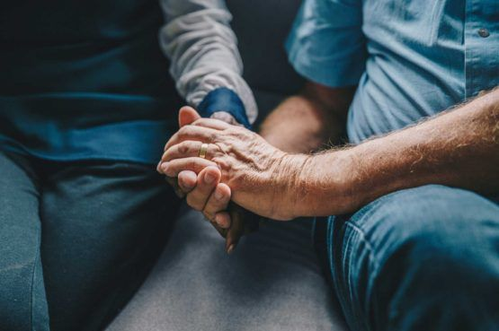 hands of older man and woman holding each other while sitting